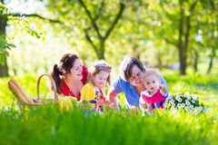 Young family with kids having picnic outdoors. Parents with two children relax in a sunny summer garden. Mother, father, little girl and baby boy eat sandwich Stock Images