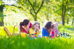 Young family with kids having picnic outdoors. Parents with two children relax in a sunny summer garden. Mother, father, little girl and baby boy eat sandwich Royalty Free Stock Images