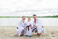 Father, mother and little son - sport family. Young family in kimono outdoors. royalty free stock images