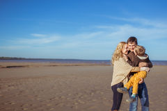 A young family kissing and embracing at the beach. The happy young parents are embracing their son who kissed the father at the beach. Clothes: casual Stock Image