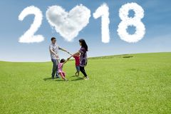 Young family laughing together in the meadow. Young family laughing together while having fun in the meadow with clouds shaped numbers 2018 and heart in the sky stock photography