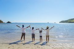 Young family lifting hands together on the beach stock image