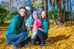 Young family with litlle girls in autumn park on Royalty Free Stock Photography