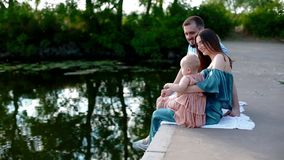 Young family with little child near the river. Beautiful portrait of happy people. Nice moment of life with a baby. Family values concept stock video footage