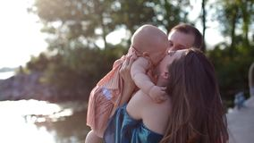 Young family with little child near the river. Beautiful portrait of happy people. Nice moment of life with a baby. Family values concept stock video