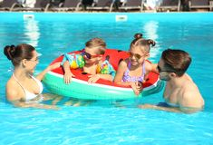 Young family with little children in swimming pool. On sunny day stock photography