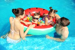 Young family with little children in swimming pool. On sunny day royalty free stock images