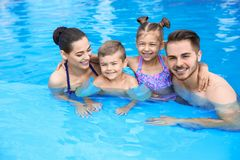 Young family with little children in swimming pool. On sunny day royalty free stock photography
