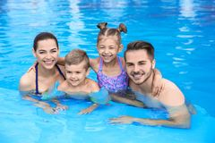 Young family with little children in swimming pool. On sunny day stock photos