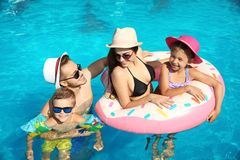 Young family with little children in swimming pool. On sunny day royalty free stock photo