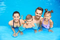 Young family with little children in swimming pool. On sunny day royalty free stock image
