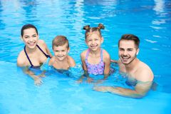 Young family with little children in swimming pool. On sunny day stock image