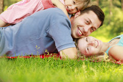Young family with little daughter lie on the grass. A young family with little daughter lie on the grass royalty free stock photography