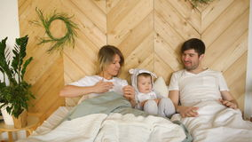 A young family with little son play on bed in the bedroom stock footage