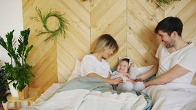 A young family with little son play on bed in the bedroom. At home Royalty Free Stock Image
