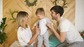 A young family with little son play in bed and kiss him smiling in the bedroom stock footage