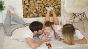 A young family with little son play on floor and kiss him smiling in the living room stock video