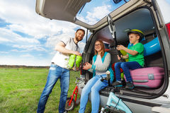 Young family loading luggage boot for the car trip Stock Photography
