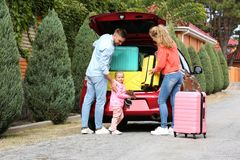 Young family loading suitcases in car trunk. Outdoors royalty free stock images