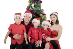 Young family with Christmas tree on studio. Young family looking at the camera and sitting together near a Christmas tree, isolated on white background Stock Photo