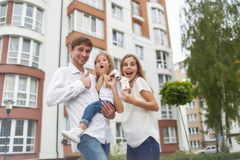 Happy family in front of new apartment building. Young family looking excited moving into their new home screaming joyfully holding keys to their apartment Stock Image