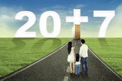 Young family looking number 2017. Image of young family standing on the road while looking number 2017 with a cross symbol Stock Images