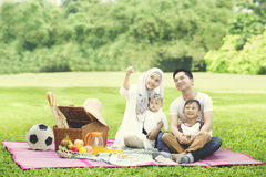 Young family looking at something in the park Stock Image