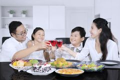 Happy family is toasting drink together at home. Young family looks happy while toasting glasses of syrup before having a dinner at home royalty free stock image