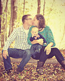 Young Family in Love. A mother and father sitting on a log in a romantic kiss while their young baby wearing an adorable bow-tie smiles with hand in his mouth