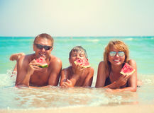 Young family lying on the beach and eating watermelon Stock Images