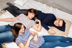 Young family lying on a bed. Mother, father and daughter lying on the bed and smiling. Family life Royalty Free Stock Photography