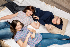 Young family lying on a bed. Mother, father and daughter lying on the bed and smiling. Family life Stock Image