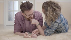 Young family lying on fluffy carpet close up. Positive young woman with curly hair pull and scratch beard of man in stock footage