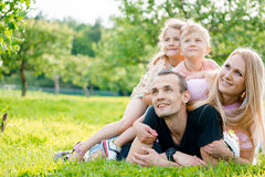 Young family lying on grass in countryside. Young big happy family lying on grass in countryside Stock Photos