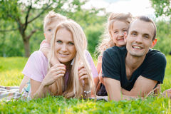 Young family lying on grass in countryside. Young big happy family lying on grass in countryside Stock Photography