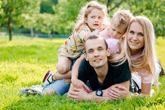 Young family lying on grass in countryside Royalty Free Stock Photos
