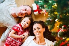 Young family lying under Christmas tree among presents, Stock Photography
