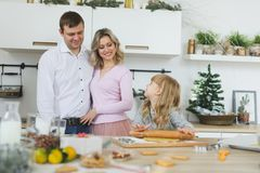 Young family making cookies at home. food, family, christmas, hapiness and people concept - smiling family making a. Food, family, christmas, hapiness and people Royalty Free Stock Photo