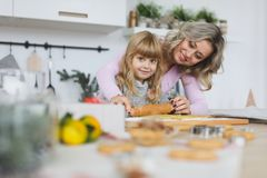 Young family making cookies at home. food, family, christmas, hapiness and people concept - smiling family making a. Food, family, christmas, hapiness and people Royalty Free Stock Images