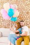 Young family man, woman and baby girl sitting on couch indoors with wooden decorative wall and multi-colored balloons with helium Royalty Free Stock Image