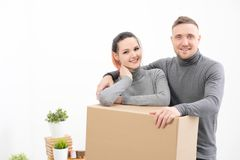 A young family, a man and a woman in gray sweaters are moving to a new apartments. Boxes with cargo on a white stock photos