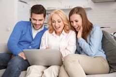 Young family with mother-in-law at home weekend browsing laptop smiling stock photo