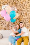 Young family man, woman and baby girl sitting on couch indoors with wooden decorative wall and multi-colored balloons with helium stock photography