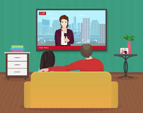 Young family man and women watching TV daily news program together in the living room. Hot news with reporter. Royalty Free Stock Image