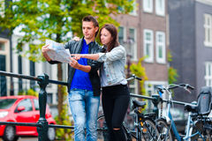 Young family with a map outdoors in Amsterdam Royalty Free Stock Photo