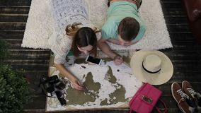 Young family marking places to visit on travel map. Top view of cheerful couple lying on the carpet in domestic interior and planning their trip around the world stock footage