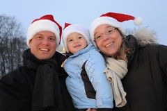 Young Family with X-mas hats Royalty Free Stock Photos
