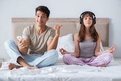 The young family meditating in the bed bedroom. Young family meditating in the bed bedroom Royalty Free Stock Image