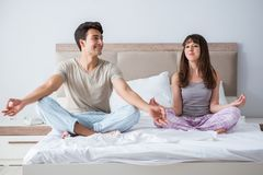The young family meditating in the bed bedroom. Young family meditating in the bed bedroom Royalty Free Stock Images