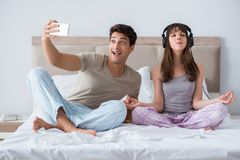 The young family meditating in the bed bedroom. Young family meditating in the bed bedroom Stock Image